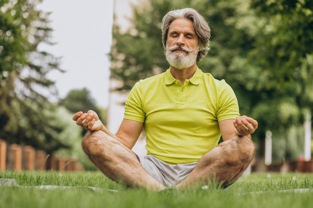 Мужчина средних лет занимается йогой на коврике в парке