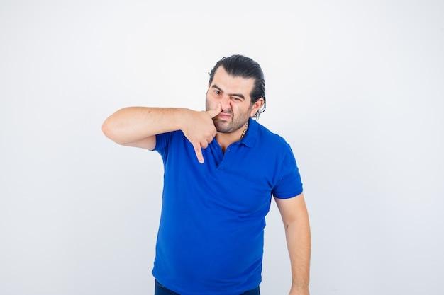 Мужчина средних лет нажимает большим пальцем на нос в футболке-поло и выглядит унылым видом спереди