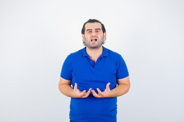 Мужчина средних лет делает вид, что держит что-то в футболке-поло, и выглядит задумчивым