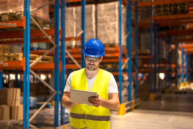 Middle aged man in protective work wear working on a tablet in large warehouse storage center