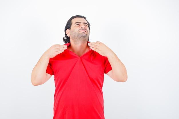 Uomo di mezza età in t-shirt rossa che tiene il colletto mentre si sente caldo e sembra annoiato, vista frontale.
