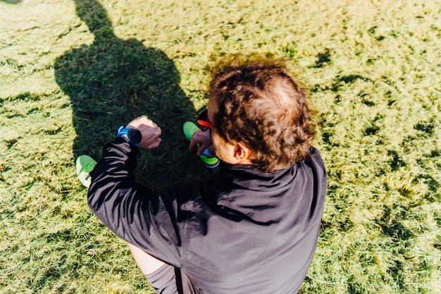 훈련 계획에서 스마트 워치를 보고 안경을 쓰고 공원에서 잔디에 앉아 중년 남자 주자