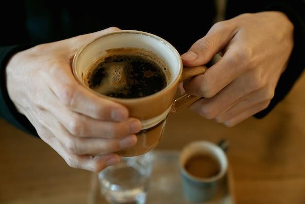カフェでエスプレッソコーヒーのカップを保持している中年男性の手。朝の儀式の概念。
