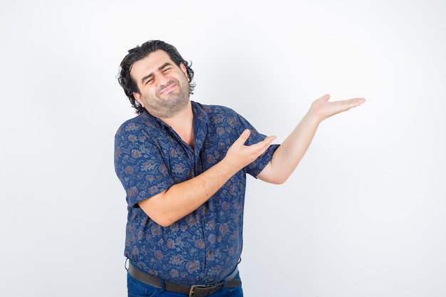 Uomo di mezza età in camicia che dà il benvenuto a qualcosa e sembra carino, vista frontale.