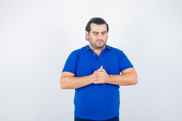 Uomo di mezza età che mostra le mani giunte in t-shirt polo e guardando sconvolto, vista frontale.