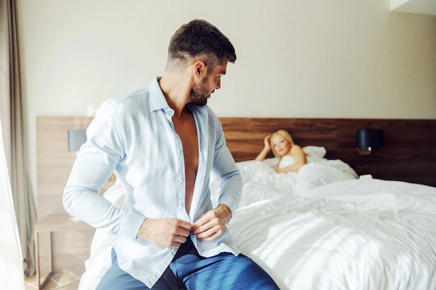 A middle-aged man sitting on the bed in a hotel and buttoning up his shirt. he was with his lover last night.