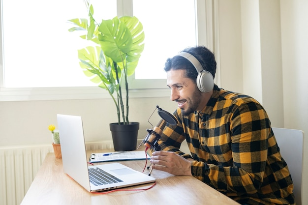 Middle-aged man sitting in front of a computer with a microphone and headphones
