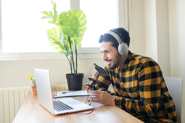 마이크와 헤드폰으로 컴퓨터 앞에 앉아 있는 중년 남성