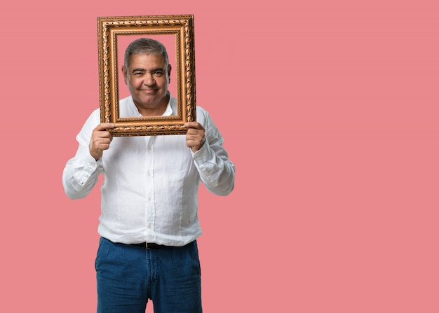 Middle aged man smiling and relaxed, looking through a frame, funny and creative photo