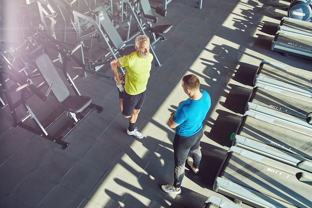 Middle aged man in sportswear warming up stretching his legs and talking with fitness instructor at