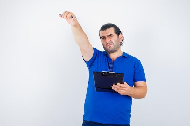 ポロtシャツに鉛筆とクリップボードを持って焦点を合わせながらカメラを見つめる中年男性。正面図。