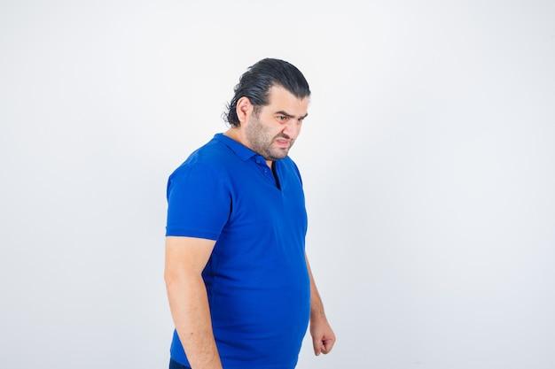 ポロtシャツで何かを見つめ、攻撃的に見える中年男性。正面図。