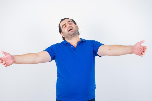 Мужчина средних лет протягивает руки в футболке-поло и выглядит расслабленным, вид спереди.