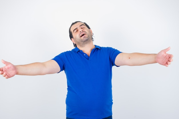 Middle aged man stretching arms aside in polo t-shirt and looking relaxed