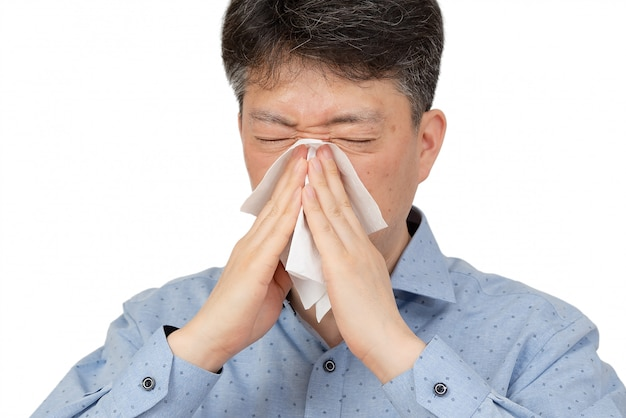 A middle-aged man suffering from rhinitis on white.