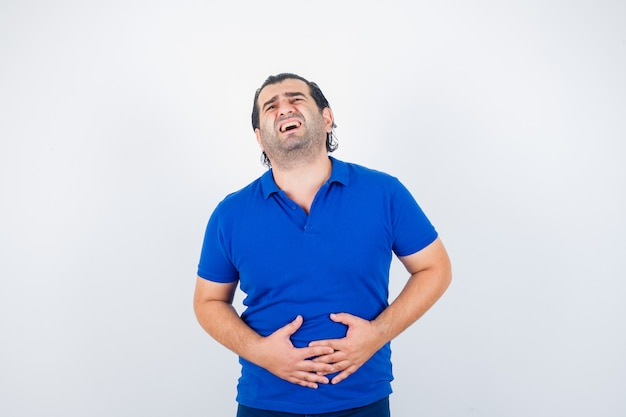 Middle aged man suffering from stomach pain in blue t-shirt and looking unwell. front view.