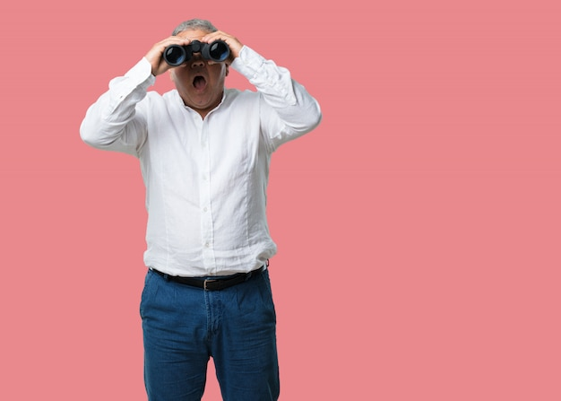 Middle aged man surprised and amazed, looking with binoculars in the distance something in