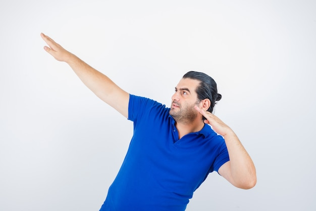 青いtシャツを着て手を伸ばして狙いを定めて集中している中年男性。正面図。