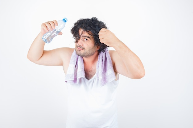 Uomo di mezza età in canottiera, asciugamano tenendo una ciocca di capelli mantenendo la bottiglia d'acqua e guardando divertente, vista frontale.
