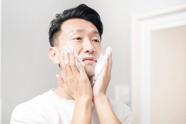 Мужчина средних лет умывает лицо пеной в умывальнике
