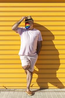 帽子、サングラス、虹色の保護マスクを身に着けている中年男性。黄色の背景にlgtb。 covid-19コンセプト