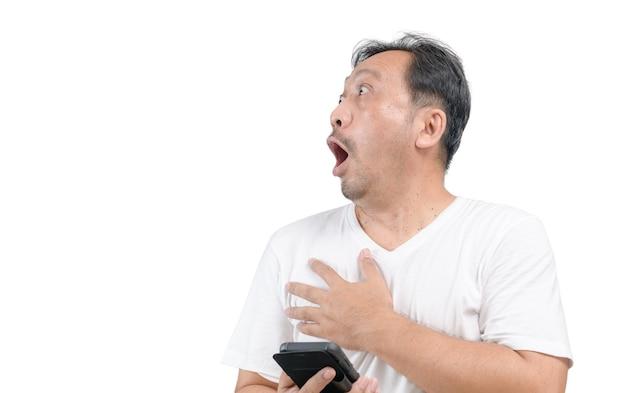 白いtシャツを着ている中年男性はスマートフォンを保持し、白い背景、感情の顔の概念に孤立して非常にショックを受けた