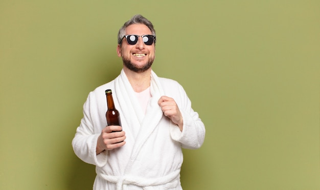 Middle aged man wearing bath robe and drinking a beer