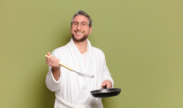 Middle aged man wearing bath robe and learning to cook with a pan