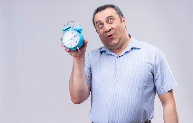 白い背景の上に立っている間青い目覚まし時計を保持している青い縦縞のシャツを着ている中年の男