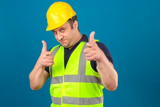 Мужчина средних лет в строительном желтом жилете и защитном шлеме, указывая указательным пальцем на синюю стену