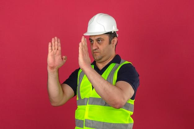 격리 된 분홍색 벽 위에 크기를 보여주는 손으로 몸짓을 지시하는 건설 노란색 조끼와 안전 헬멧을 착용하는 가운데 세 남자