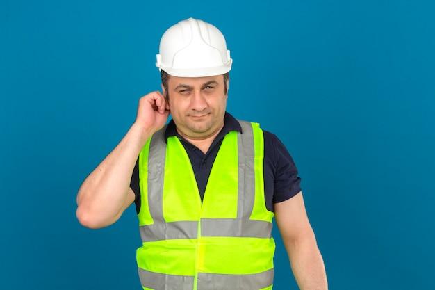 孤立した青い壁に建設黄色のベストと耳に不審な表情に触れる安全ヘルメットを身に着けている中年の男
