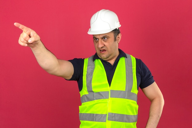 Middle aged man wearing construction yellow vest and safety helmet pointing to the side displeased and frustrated over isolated pink wall