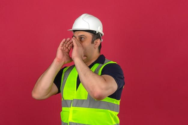 Uomo di mezza età che indossa maglia gialla da costruzione e casco di sicurezza che urla qualcosa e che tiene le mani vicino alla sua bocca aperta sopra la parete rosa isolata