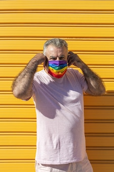 Middle-aged man wearing a hat, sunglasses and a rainbow-colored protective mask. lgtb on yellow background. covid-19 concept