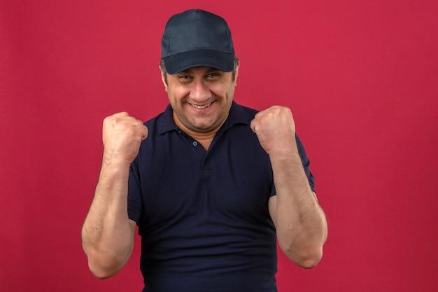 ポロシャツとキャップを着て中年の男が分離されたピンクの壁に勝者のような拳を上げる幸せを探して
