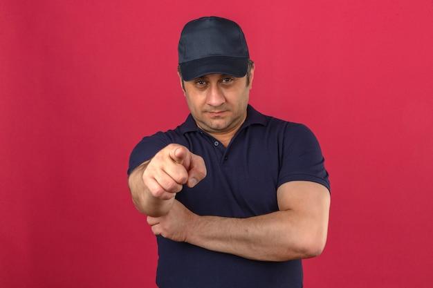 Мужчина средних лет в рубашке поло и кепке указывает на камеру с серьезным лицом над изолированной розовой стеной