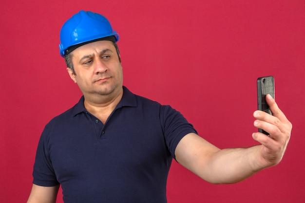 中年男性がポロシャツと携帯電話で立っている安全ヘルメットを身に着けて、孤立したピンクの壁を越えてselfieを取る