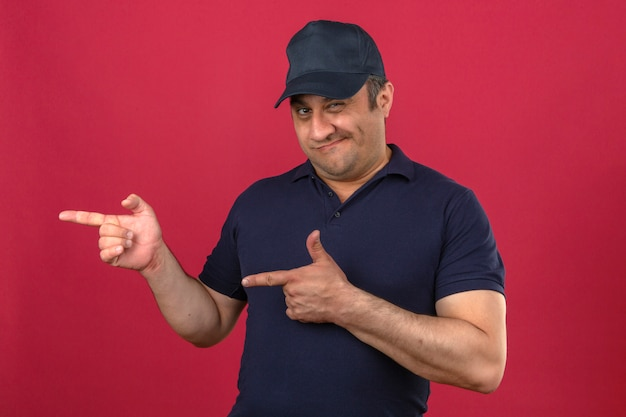 Middle aged man wearing polo shirt and cap pointing with fingers to the side smiling over isolated pink wall