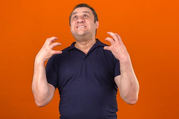 Pugni di serraggio da portare della camicia di polo dell'uomo invecchiato centrale che si arrabbiano sopra la parete arancione isolata