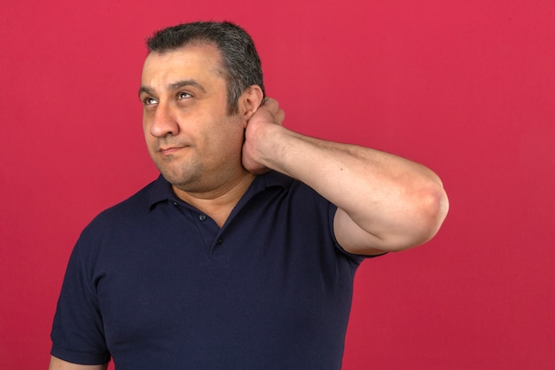 Middle aged man wearing polo shirt feeling puzzled and confused scratching head and looking to the side over isolated pink wall