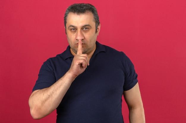 Мужчина средних лет в рубашке поло делает жест молчания над изолированной розовой стеной