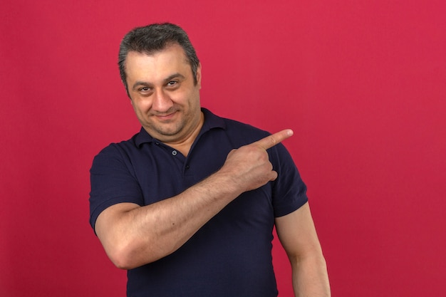 Middle aged man wearing polo shirt pointing to the side with smile on face over isolated pink wall