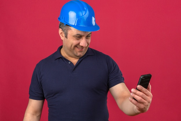 Middle aged man wearing polo shirt and safety helmet looking at the screen of mobile phone with big smile on face over isolated pink wall