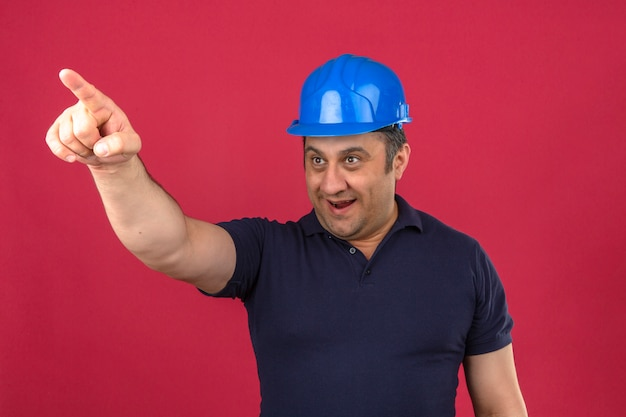 Middle aged man wearing polo shirt and safety helmet pointing to the side with happy face and smiling over isolated pink wall
