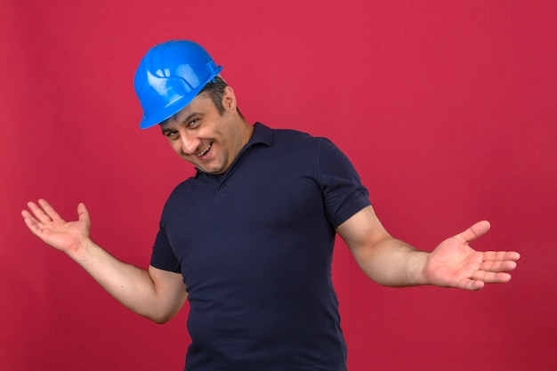 Middle aged man wearing polo shirt and safety helmet smiling stretches his hands forward as if pleased to meet someone over isolated pink wall