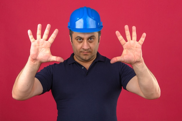 Middle aged man wearing polo shirt and safety helmet with smile on face and showing number ten with fingers over isolated pink wall