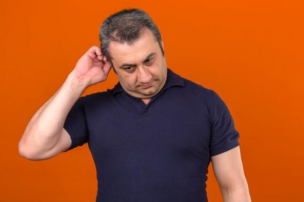 孤立したオレンジ色の壁を真面目な顔で考えながら耳に触れるポロシャツを着ている中年の男
