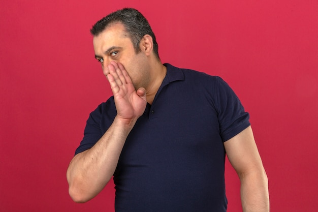 Camicia di polo d'uso dell'uomo di mezza età che bisbiglia un segreto che copre la sua bocca di sua mano sopra la parete rosa isolata