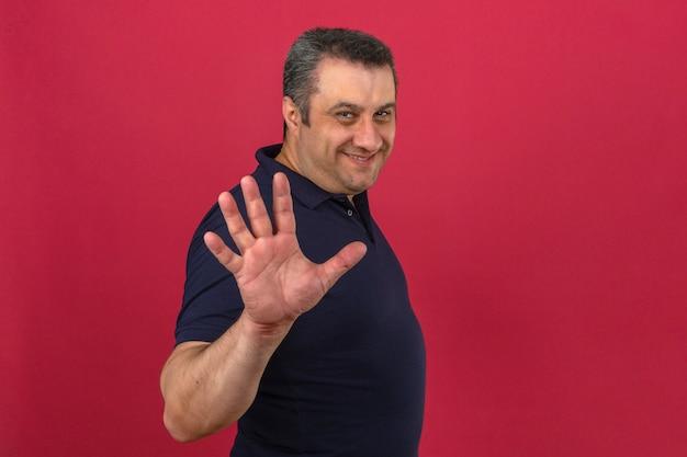 顔に笑顔でポロシャツを着て、孤立したピンクの壁に指で数5を示す中年の男